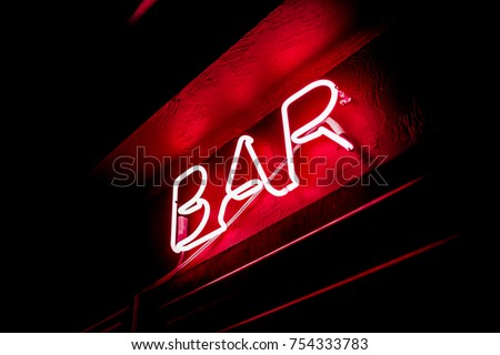 Neon inscription BAR on the wall. Neon inscription BAR in different colors. Multicolored neon inscription BAR on dark background #754333783
