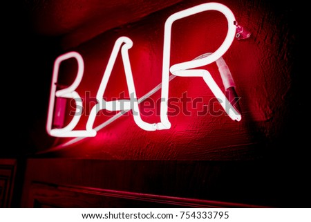 Neon inscription BAR on the wall. Neon inscription BAR in different colors. Multicolored neon inscription BAR on dark background #754333795