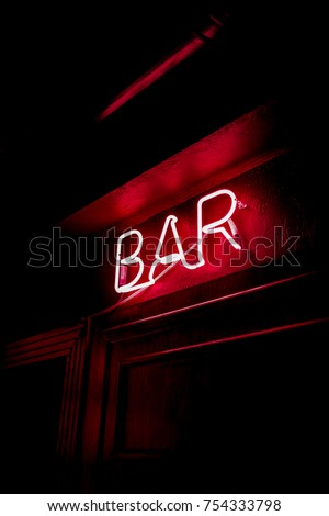 Neon inscription BAR on the wall. Neon inscription BAR in different colors. Multicolored neon inscription BAR on dark background #754333798