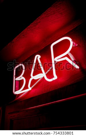 Neon inscription BAR on the wall. Neon inscription BAR in different colors. Multicolored neon inscription BAR on dark background #754333801