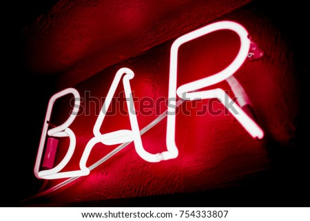 Neon inscription BAR on the wall. Neon inscription BAR in different colors. Multicolored neon inscription BAR on dark background #754333807