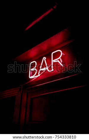 Neon inscription BAR on the wall. Neon inscription BAR in different colors. Multicolored neon inscription BAR on dark background #754333810