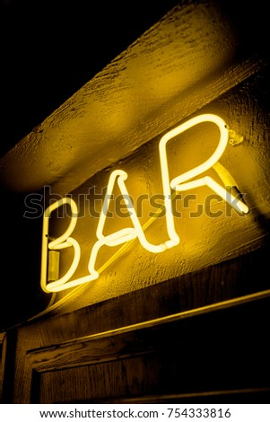 Neon inscription BAR on the wall. Neon inscription BAR in different colors. Multicolored neon inscription BAR on dark background #754333816