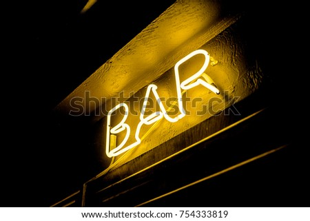 Neon inscription BAR on the wall. Neon inscription BAR in different colors. Multicolored neon inscription BAR on dark background #754333819
