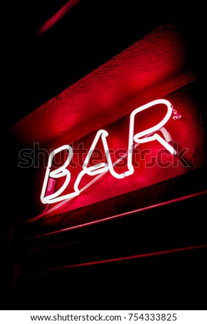 Neon inscription BAR on the wall. Neon inscription BAR in different colors. Multicolored neon inscription BAR on dark background #754333825