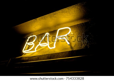 Neon inscription BAR on the wall. Neon inscription BAR in different colors. Multicolored neon inscription BAR on dark background #754333828