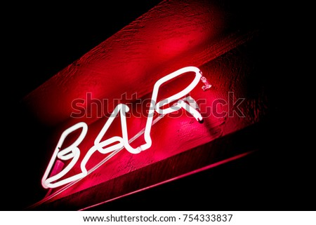 Neon inscription BAR on the wall. Neon inscription BAR in different colors. Multicolored neon inscription BAR on dark background #754333837