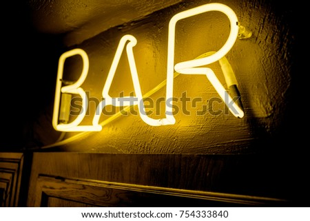 Neon inscription BAR on the wall. Neon inscription BAR in different colors. Multicolored neon inscription BAR on dark background #754333840