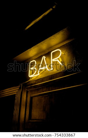 Neon inscription BAR on the wall. Neon inscription BAR in different colors. Multicolored neon inscription BAR on dark background #754333867