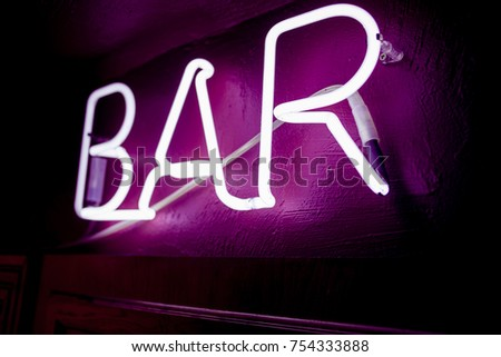 Neon inscription BAR on the wall. Neon inscription BAR in different colors. Multicolored neon inscription BAR on dark background #754333888