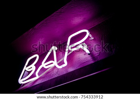 Neon inscription BAR on the wall. Neon inscription BAR in different colors. Multicolored neon inscription BAR on dark background #754333912