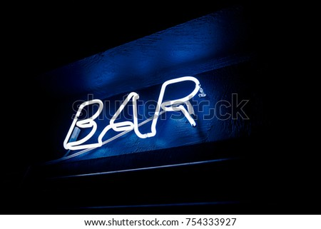 Neon inscription BAR on the wall. Neon inscription BAR in different colors. Multicolored neon inscription BAR on dark background #754333927