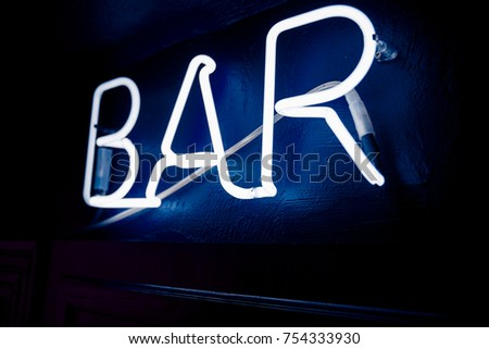 Neon inscription BAR on the wall. Neon inscription BAR in different colors. Multicolored neon inscription BAR on dark background #754333930