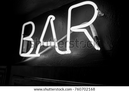 Neon inscription BAR on the wall. Neon inscription BAR in different colors. Multicolored neon inscription BAR on dark background. Black and white photo #760702168