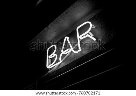 Neon inscription BAR on the wall. Neon inscription BAR in different colors. Multicolored neon inscription BAR on dark background. Black and white photo #760702171