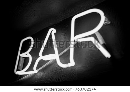 Neon inscription BAR on the wall. Neon inscription BAR in different colors. Multicolored neon inscription BAR on dark background. Black and white photo #760702174
