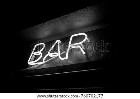 Neon inscription BAR on the wall. Neon inscription BAR in different colors. Multicolored neon inscription BAR on dark background. Black and white photo #760702177