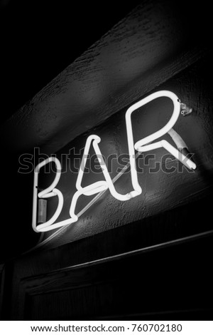 Neon inscription BAR on the wall. Neon inscription BAR in different colors. Multicolored neon inscription BAR on dark background. Black and white photo #760702180