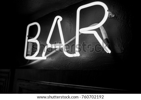 Neon inscription BAR on the wall. Neon inscription BAR in different colors. Multicolored neon inscription BAR on dark background. Black and white photo #760702192