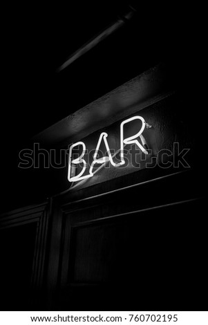 Neon inscription BAR on the wall. Neon inscription BAR in different colors. Multicolored neon inscription BAR on dark background. Black and white photo #760702195