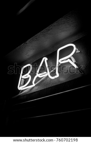 Neon inscription BAR on the wall. Neon inscription BAR in different colors. Multicolored neon inscription BAR on dark background. Black and white photo #760702198