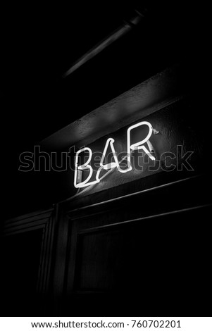Neon inscription BAR on the wall. Neon inscription BAR in different colors. Multicolored neon inscription BAR on dark background. Black and white photo #760702201