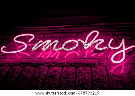 Neon inscription SMOKY on the wall. Neon inscription SMOKY in different colors. Multicolored neon inscription SMOKY on dark background #678793219