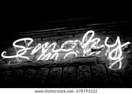 Neon inscription SMOKY on the wall. Neon inscription SMOKY in different colors. Multicolored neon inscription SMOKY on dark background #678793222