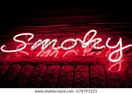 Neon inscription SMOKY on the wall. Neon inscription SMOKY in different colors. Multicolored neon inscription SMOKY on dark background #678793225