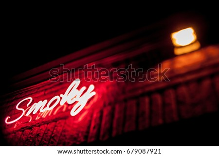Neon inscription SMOKY on the wall. Neon inscription SMOKY in different colors. Multicolored neon inscription SMOKY on dark background #679087921