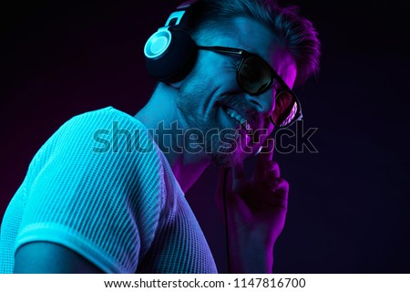 Neon light portrait of bearded smiling man in headphones, sunglasses, white t-shirt. Listening to music  #1147816700