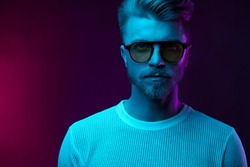 Neon light studio portrait of serious man model with mustaches and beard in sunglasses and white t-shirt