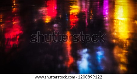 Neon lights and shadows in New York City. NYC streets after rain with reflections on wet asphalt.
