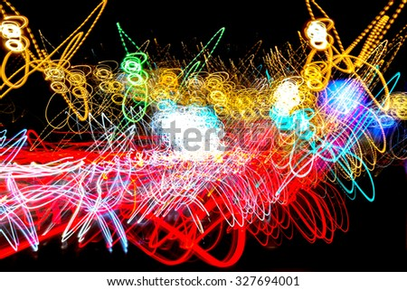 Neon lights form an abstract light painting image as they merge and collide against a black void like background, Multicolored light streaks of red, yellow, white, and pink