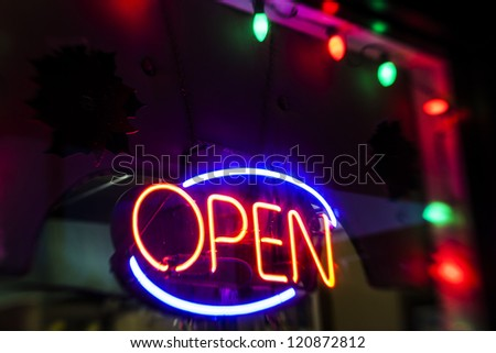 Neon Open sign with Christmas lights and decorations shot at night with a tilt shift lens.