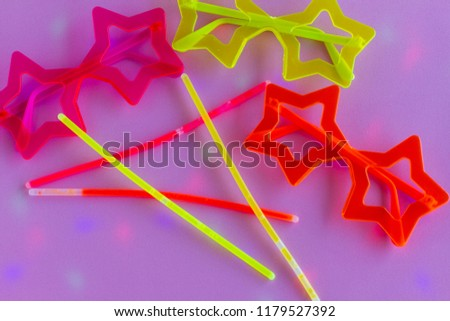 Neon Party supplies on pink background. Colored led party lights - Photo booth Props. Copy Space.  Party background