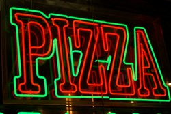 Neon pizza sign on the streets of New York