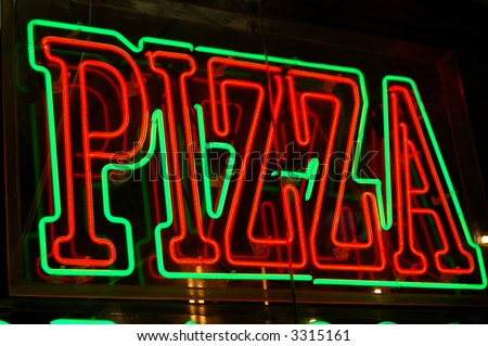 Neon pizza sign on the streets of New York - stock photo