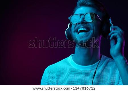 Neon portrait of bearded smiling man in headphones, sunglasses, white t-shirt. Listening to music