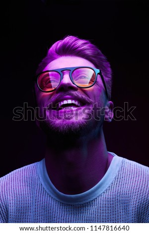Neon portrait of smiling man model with mustaches and beard in orange sunglasses and white t-shirt