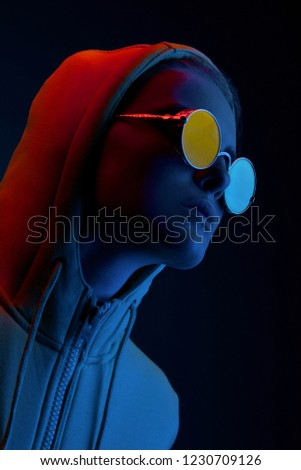 Neon portrait of young woman in round sunglasses. Studio shot  #1230709126