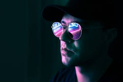 Neon reflection in glasses. Man in fluorescent light from city led sign. Mysterious cool model in futuristic cyberpunk portrait. Guy in sunglasses. Techno rave party disco art. Dark black background.