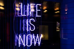 Neon Sign Glowing At Night Behind Glass: Life Is Now.