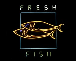Neon sign in display window of restaurant that serves fresh fish, with black background