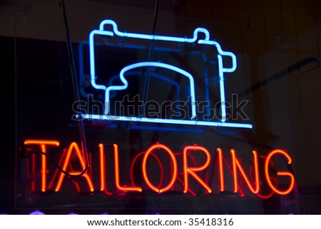 Neon sign in window of a New York City garment district tailor shop.