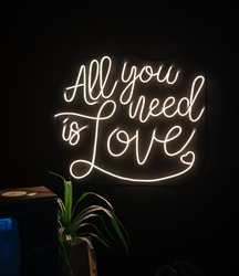 Neon sign inscription all you need is love on a dark background. Love concept