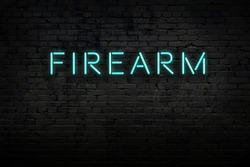 Neon sign on brick wall at night. Inscription firearm