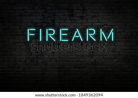 Photo of  Neon sign on brick wall at night. Inscription firearm