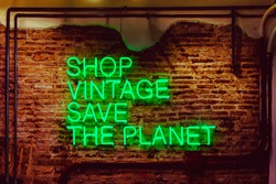 Neon sign. Shop vintage, save the planet. Beautiful green neon against a red brick wall. Taken at vintage shop in Barcelona.