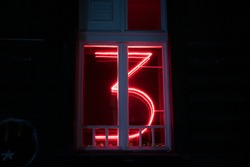 Neon sign signifying number 3 in a bar room window, closeup